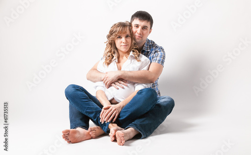 Portrait of man hugging pregnant wife sitting on floor