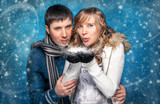 Closeup portrait of young couple blowing snowflakes from hands