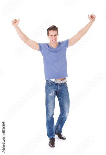 Portrait Of Excited Young Man With Hand Raised