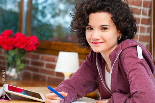 Cute student sitting at table with homework.