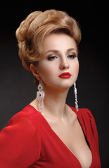 Portrait of a beautiful elegant woman in a red dress with a hair