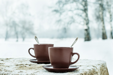 Two cups of tea on background of a winter landscape