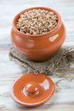 Ceramic pot with boiled buckwheat over wooden background