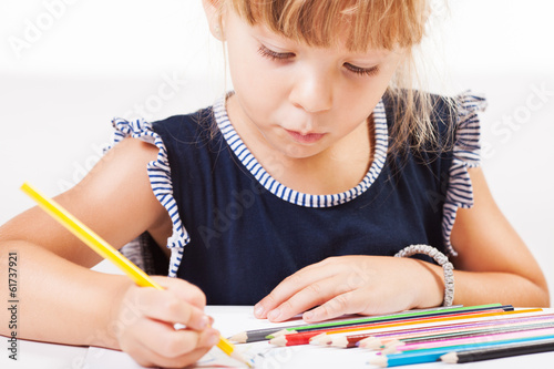 Cute little girl drawing with colored pencils at home.