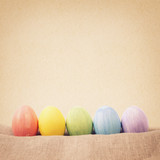 color egge in a row in from of paper background