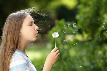 teenage girl blowing a dandelion