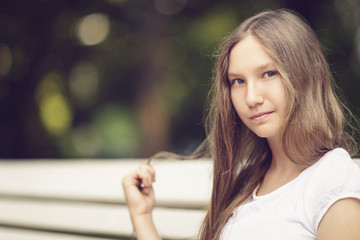 young teenage girl sitting on bench