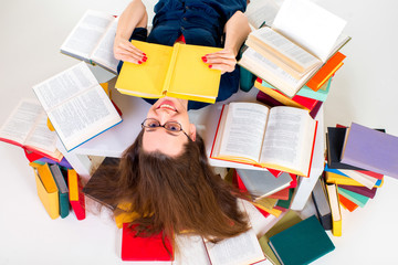 Young and smart girl lying with book surrounded by colorful book