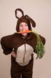 Frau im Hasenkostüm isst Möhre