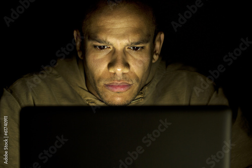 Man concentrating on his laptop late at night