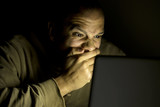 Man looking in shock at his laptop late at night