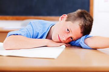 Schoolboy resting in classroom