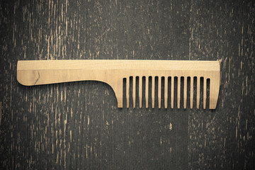 Wooden comb on a gray background. Vintage style