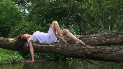 Brunette posing for camera on a fallen tree
