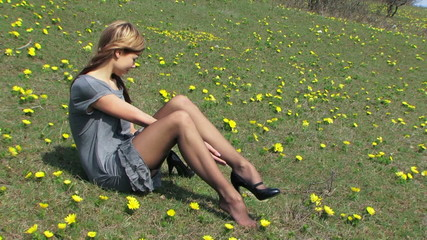 Young lady wearing a dress and high heels in a field