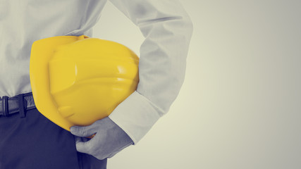 Businessman carrying a yellow hardhat