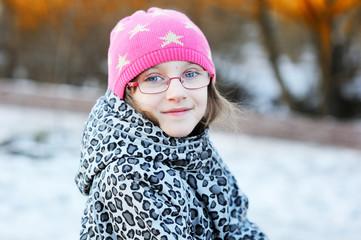 Outdoor portrait of child girl in pink cap