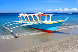 Tropical beach and traditional Philippines boat on it