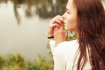 beautiful girl in profile near the lake in the summer