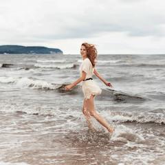 Happy beautiful girl running on the beach