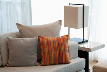 pillows on the sofa against the window