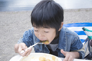 boy eating curry and rice by lakeside