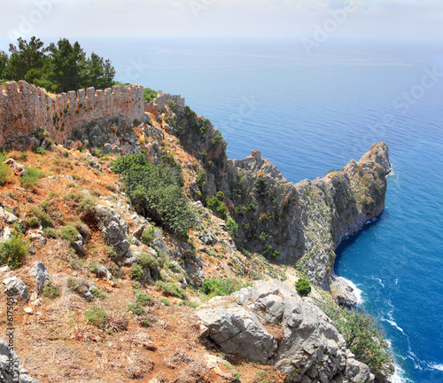 rocky headland in sea and fortress wall in Alanya
