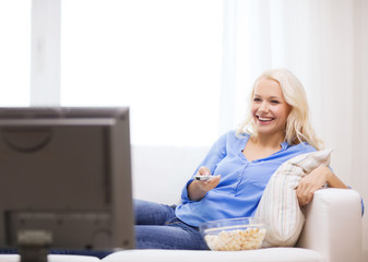 young girl with popcorn watching movie at home