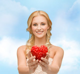 smiling woman giving small red heart