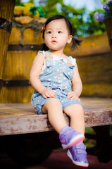 Cute Asian little girl sitting on a truck full of flowers
