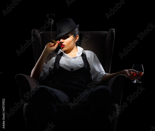 Young woman with cigar and brandy glass on chair