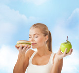 happy woman smelling hamburger and holding apple