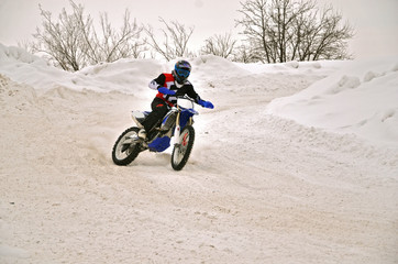 Winter motocross racer on a motorcycle turns with the slope and