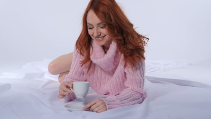 Red-haired girl drinking coffee lying on the bed