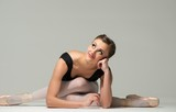 Beautiful young ballerina dancer sitting on a floor