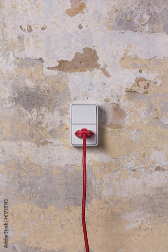 White socket with red wire on grungy wall