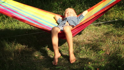 Little Boy enjoys warm sun rays in hammock