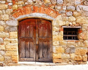Medieval stone house with rustic door, Tuscany, Italy