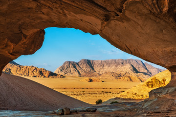 View through a rock arch in the desert of Wadi Rum
