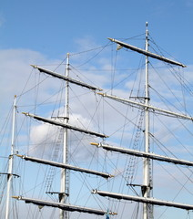 Masts of a sailing boat against a blue sky