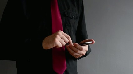 Businessman taping text message on his smartphone.
