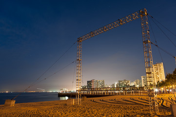 Large metal frame on the beach at night