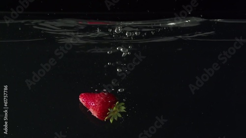 Two strawberryes  drop into water in slowmotion