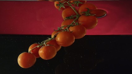 tomatoes on a branch under water in slowmotion