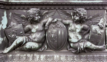 Bronze relief of cherubs holding shields
