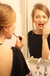 Redhead pretty woman applying lipstick and looking at the mirror