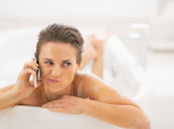 Concerned young woman in bathtub talking cell phone