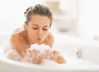 Young woman playing with foam in bathtub