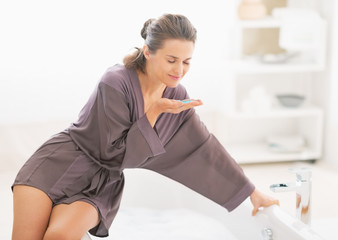 Happy young woman smelling bath salt