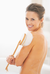 Portrait of smiling young woman in bathtub using body brush